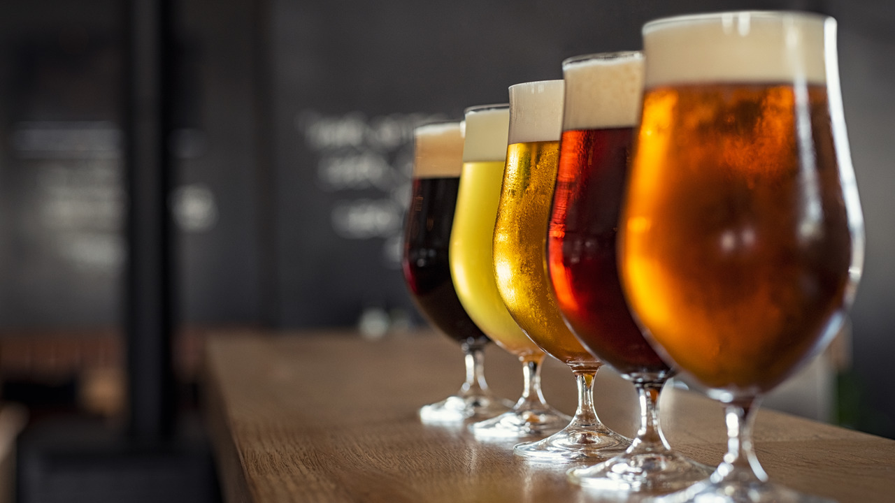 A photograph of five glasses of beer