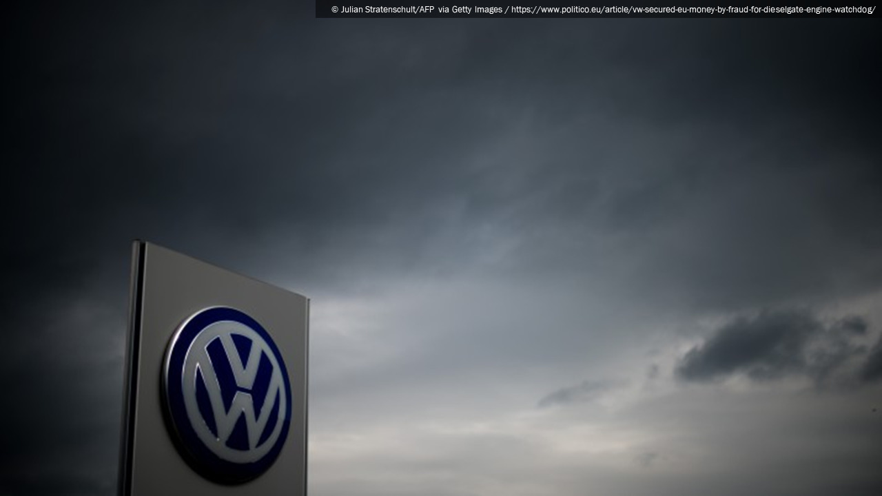 Photograph of a Volkswagen dealership sign beneath a cloudy gray sky