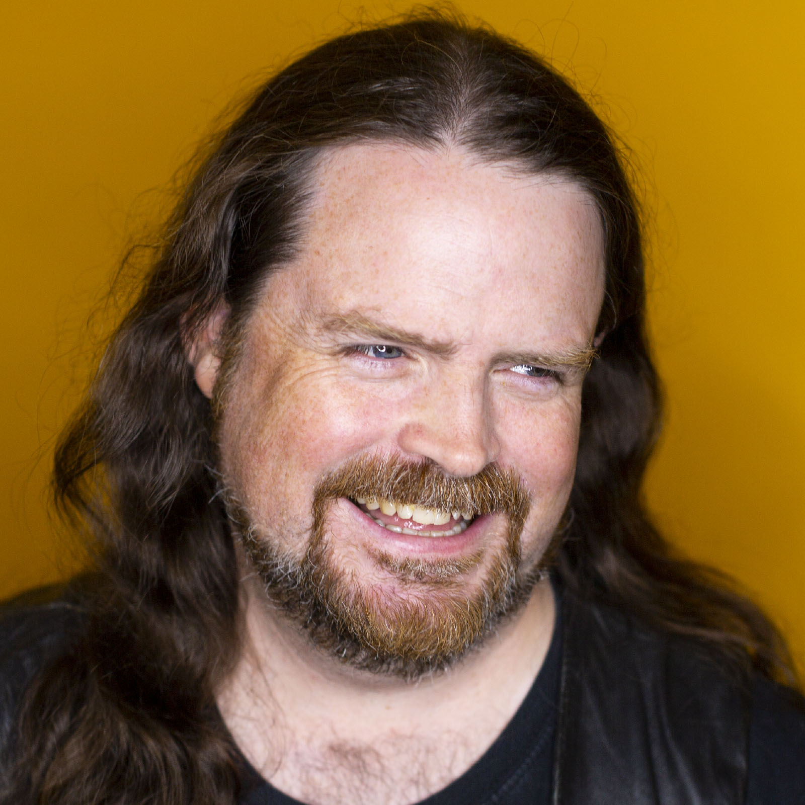 Studio headshot of Dylan Beattie in front of a yellow background.